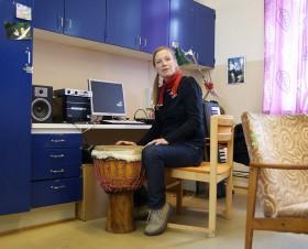 Anna Gustavsson sittandes vid bongotrumma på sitt arbetsrum