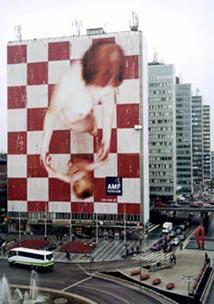 Stor bild på husfasad; naken kvinna dansandes med litet barn