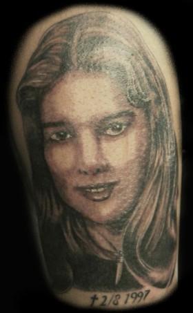Kvinnoansikte tatuerat på ben