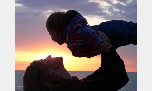 Bild av mor och barn på strand i solnedgång. Personerna på bilden är inte de samma som de i artikeln.