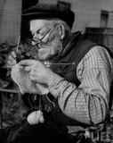 En äldre man som stickar, England cirka 1940.